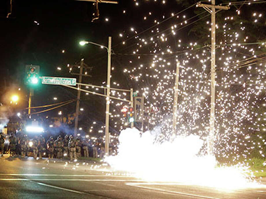 A device deployed by police goes off in the street as police and protesters clash Wednesday, Aug. 13, 2014, in Ferguson, Mo. Authorities in the St. Louis suburb where an unarmed black teen was shot and killed by a police officer have used tear gas to try to disperse protesters after flaming projectiles were thrown from the crowd. Photo: Jeff Roberson, AP / AP2014