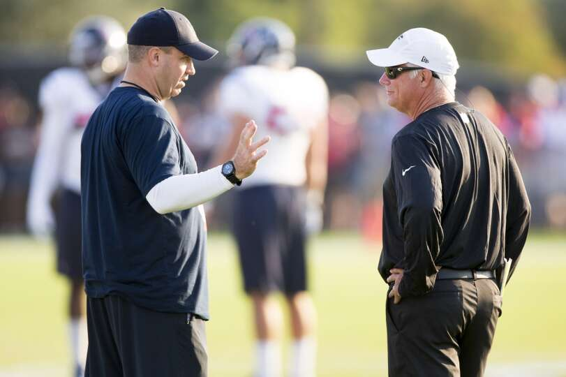 Texans head coach Bill O'Brien, left, talks to Atlanta Falcons head coach Mike Smith during a joint