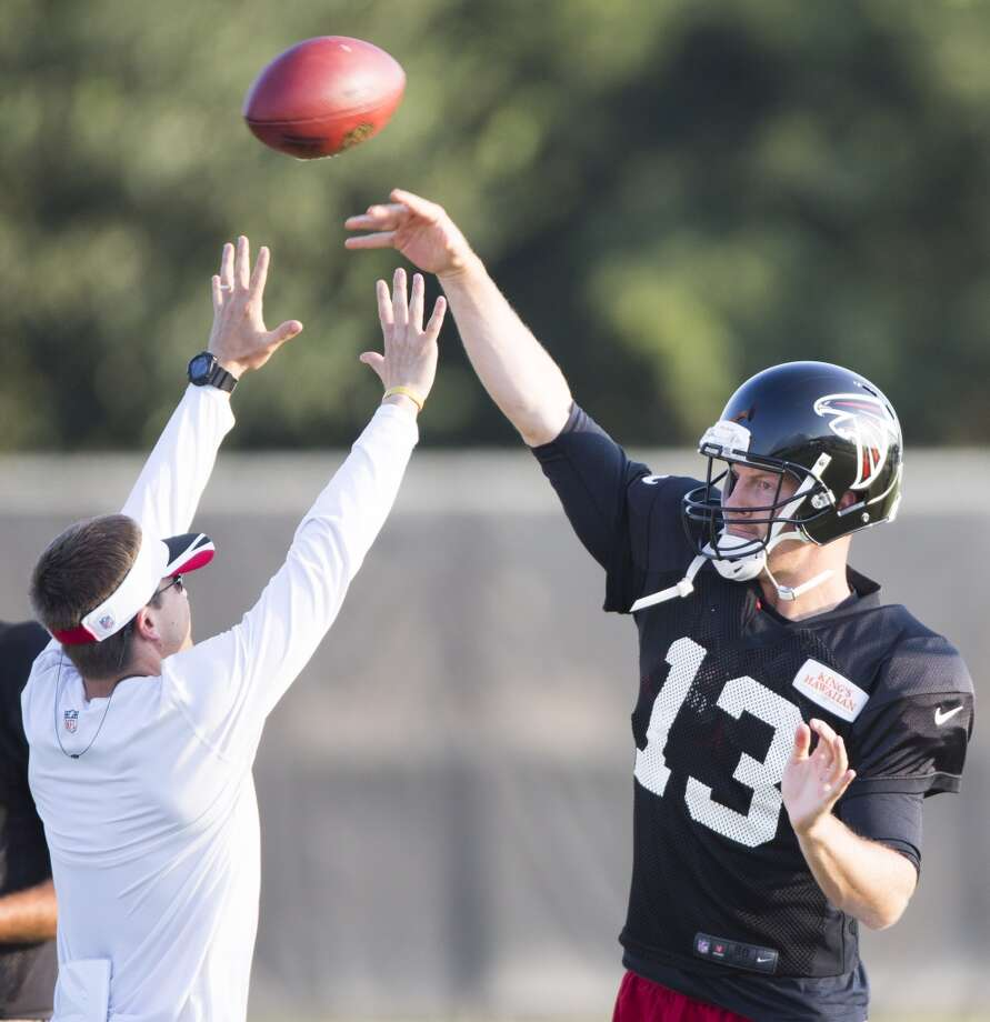 Atlanta Falcons quarterback T.J. Yates (13) throws a pass over quarterbacks coach Glenn Thomas during a joint practice. Photo: Brett Coomer, Houston Chronicle