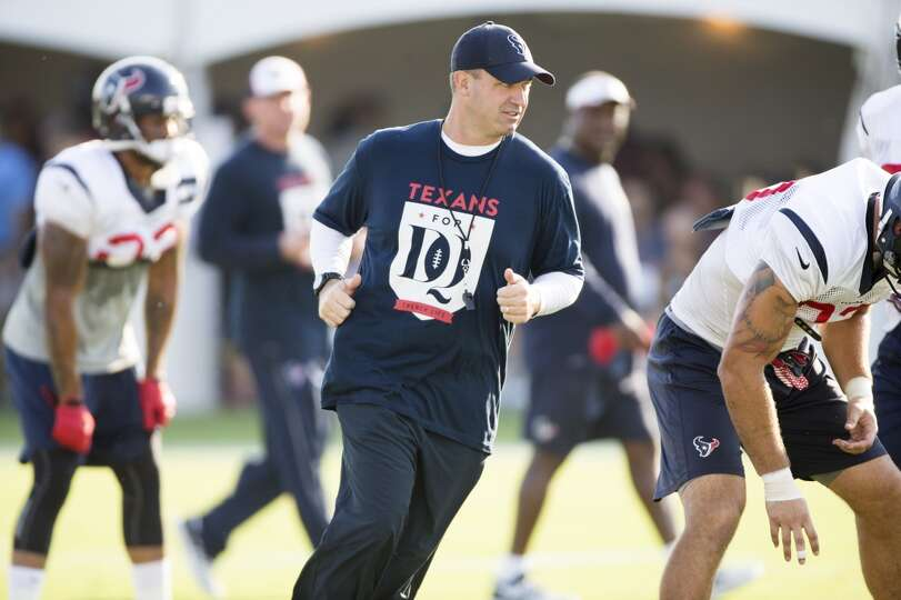 Texans head coach Bill O'Brien jogs around the Texans offense.