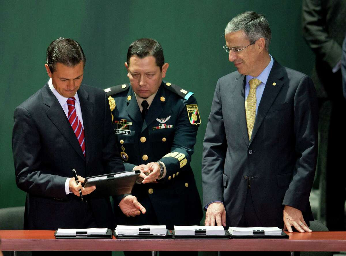 Mexican President Enrique Peña Nieto, left, is accompanied by House Speaker Jose Gonzalez Morfin, right, as he signs into law the nation's energy reforms at Mexico City's National Palace.