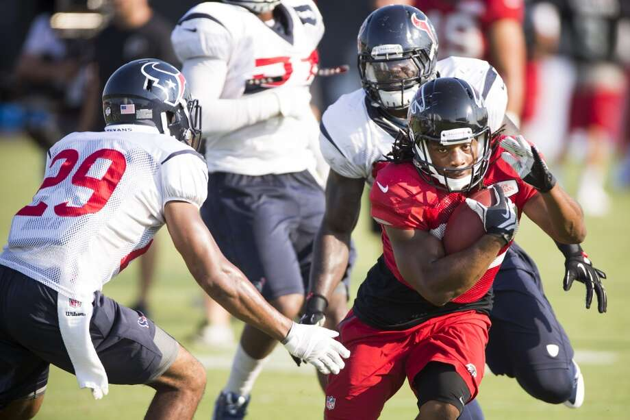 Atlanta Falcons running back Jacquizz Rodgers (32) runs the football against Texans safety Jawanza Starling (29) and outside linebacker Whitney Mercilus (59). Photo: Brett Coomer, Houston Chronicle