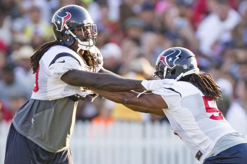 Texans linebacker Jadeveon Clowney, left, works with Texans linebacker Paul Hazel.