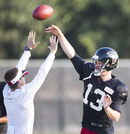 Atlanta Falcons quarterback T.J. Yates (13) throws a pass over quarterbacks coach Glenn Thomas durin