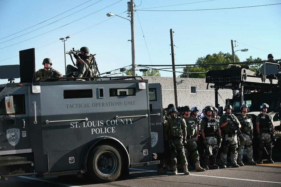 FERGUSON, MO - AUGUST 13:  Police stand watch as demonstrators protest the shooting death of teenager Michael Brown on August 13, 2014 in Ferguson, Missouri. Brown was shot and killed by a Ferguson police officer on Saturday. Ferguson, a St. Louis suburb, is experiencing its fourth day of violent protests since the killing. Photo: Scott Olson, Getty Images / 2014 Getty Images