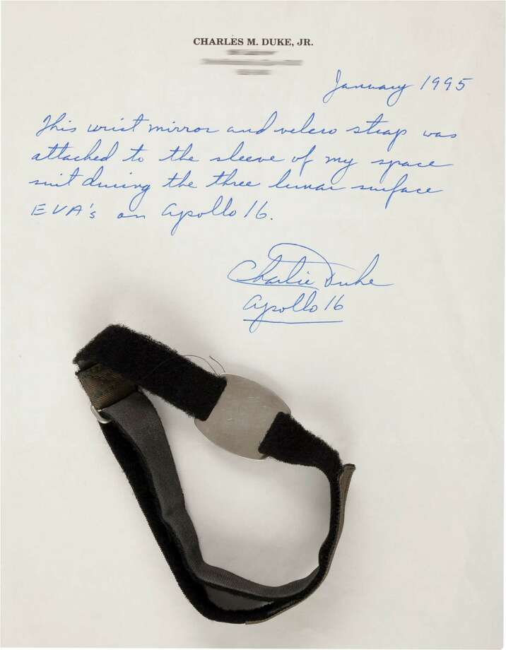 """Apollo 16 Lunar Module Flown and Surface-Used Wrist Mirror with Watch Strap Originally from the Personal Collection of Mission Lunar Module Pilot Charlie Duke, with Signed Photo and LOA.A polished metal disc, 1.375"""" x 1.25"""" overall with the part number printed on the back of """"SDB 12100086-001"""" and serial number """"1010"""". This was worn on the outside of Duke's spacesuit on his right wrist with his watch. There are numerous surface photos available (several included) of this item taken during the three surface EVAs which total more than twenty hours. It is likely that some of the grayish cast could be some of the lunar dust that covered Duke's spacesuit. Photo: Heritage Auctions"""