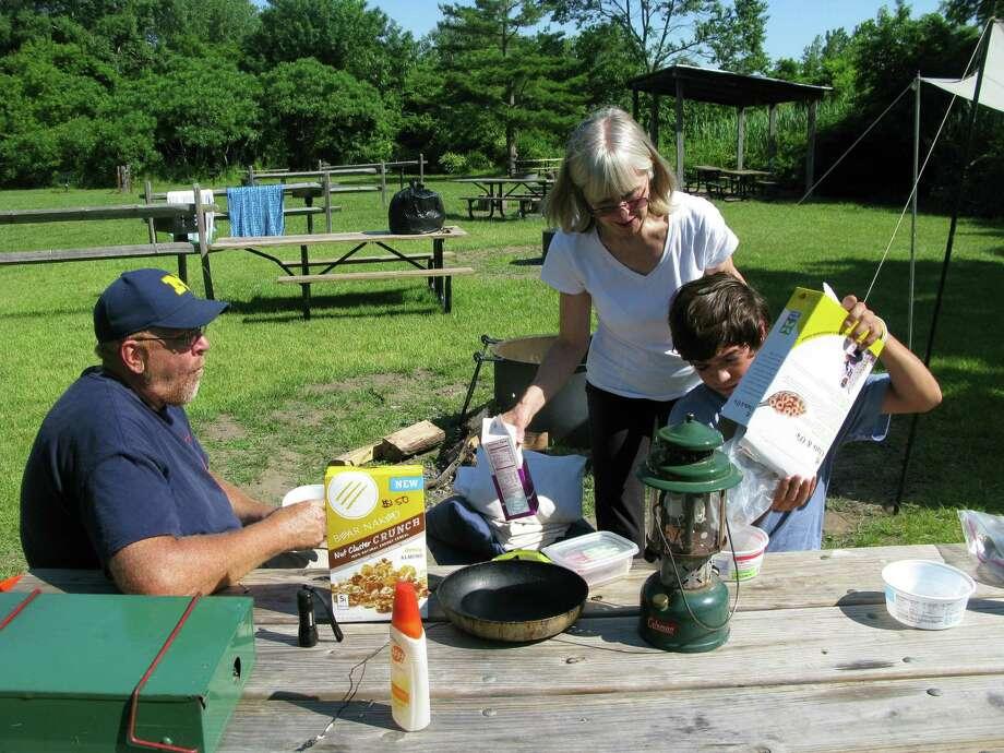Steve Kass (left), his wife, Beth, and son Kyle of Carol Stream, Illinois, eat breakfast at Floyd Bennett Field. Photo: Josh Noel / Chicago Tribune / Chicago Tribune