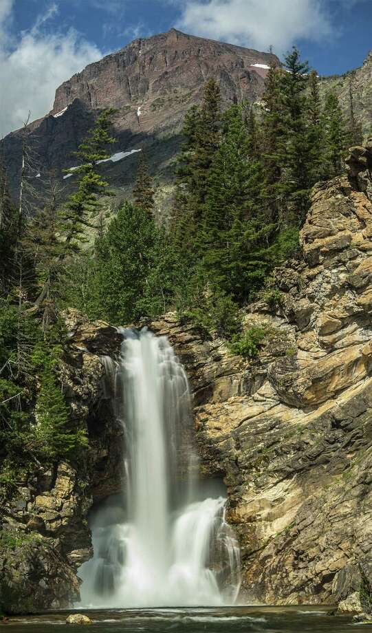 Against the backdrop of Rising Wolf Mountain, Running Eagle Falls drops about 40 feet into the stream below. This waterfall also is called Trick Falls because of the secondary waterfall in the middle. Photo: Photos By Joshua Trudell / For The Express-News