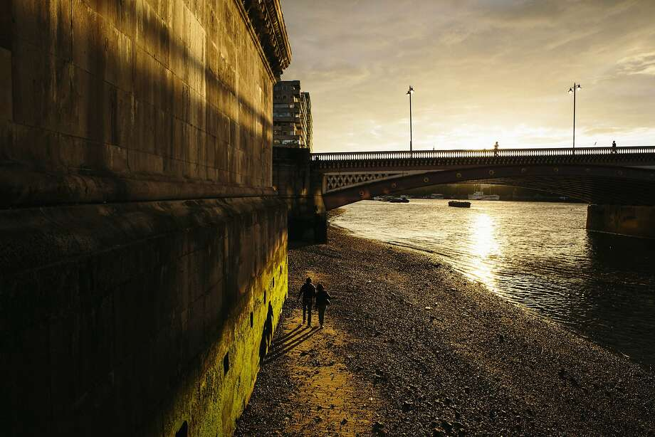 A couple make their way along the Thames River near Blackfriars Bridge at sunset in London. Photo: David Azia, Associated Press