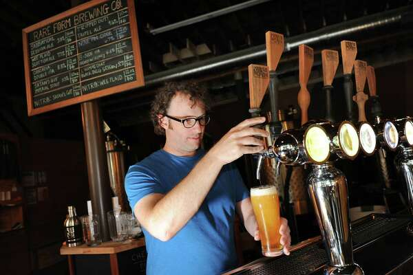 Owner Kevin Mullen draws a Sabbatical Session Ale on Thursday, Aug. 7, 2014, at Rare Form Brewing Company in Troy, N.Y. Mullen owns the business with his wife Jenny Kemp. (Cindy Schultz / Times Union)
