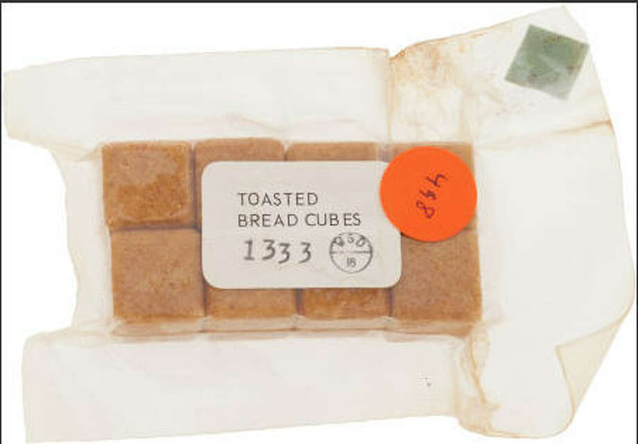 "Apollo 17 Flown ""Toasted Bread Cubes"" Space Food Originally from the Personal Collection of Mission Commander Gene Cernan, with Signed COA. A sealed flexible pouch, 4.75"" x 3"" x 0.75"" overall, with a label on one side: ""TOASTED BREAD CUBES/ 1333"" and a ""Serial No. FAY965"" sticker on the other as well as a piece of blue (Ron Evans) Velcro for attachment to the spacecraft. Unlike the above peaches, these were made to be eaten as is. From the Steven R. Belasco Collection of Space Memorabilia.  Photo: Heritage Auctions"