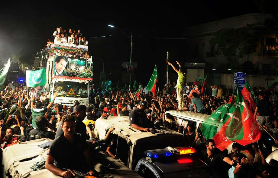 A truck carrying former cricket star Imran Khan (left) leads a protest march heading from Lahore to Islamabad. Photo: Asif Hassan, AFP/Getty Images
