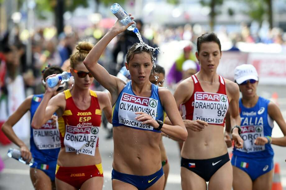 Showering on the run, er, walk:Ukraine's Lyudmila Olyanovska douses herself during the women's 20-kilometer race walk at the 