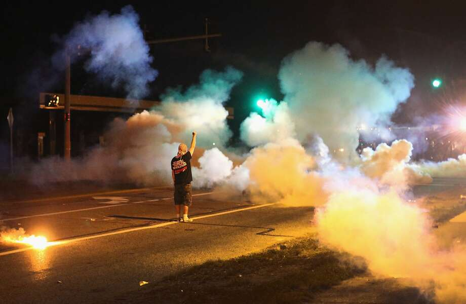 An ugly night in Ferguson: A demonstrator protesting the shooting death of teenager Michael Brown stands his ground as police 