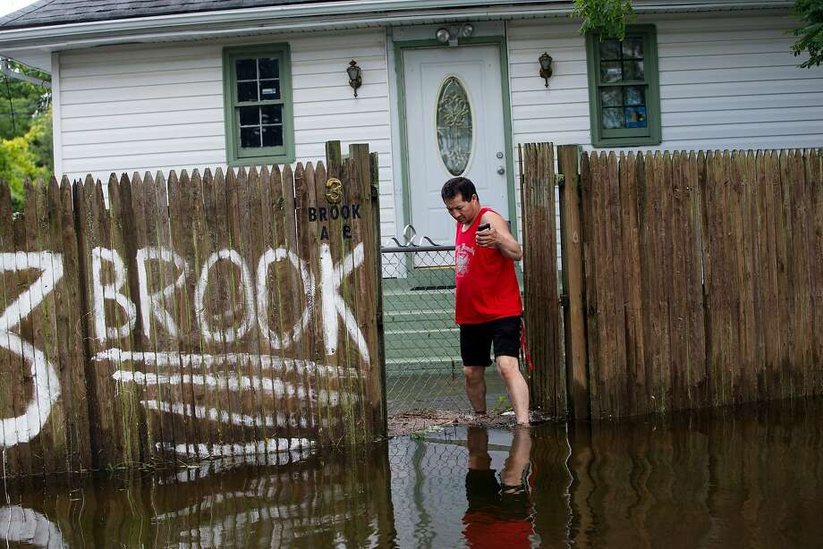 Suburban New York drenched: Brook Avenue in Bay Shore, N.Y., is more like Creek Avenue after heavy rains and flash 