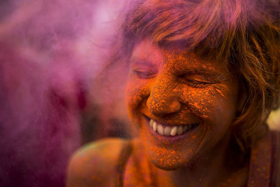 Colored powder coats the face of a Monsoon Holi Festival reveler in Madrid. The festival is based on the Hindu spring festival Holi, also known as the festival of colors, in which participants dust each other with brightly hued corn starch and dyes. Photo: Andres Kudacki, Associated Press