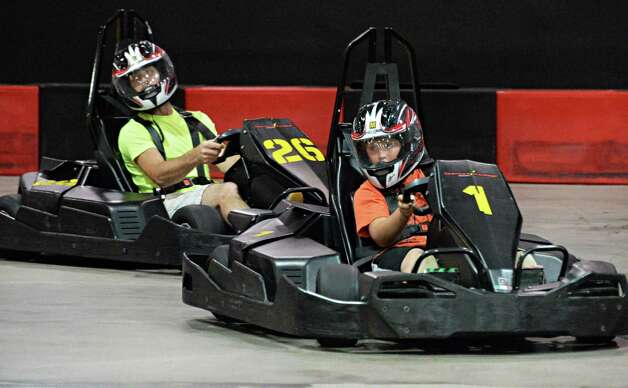 Christopher Bee of Voorheesville, left, trails behind his son Cameron Bee, 9, as they race go-carts at FasTrax Raceway in Crossgates Commons Tuesday July 29, 2014, in Albany, NY.  (John Carl D'Annibale / Times Union) Photo: John Carl D'Annibale / 00027899A