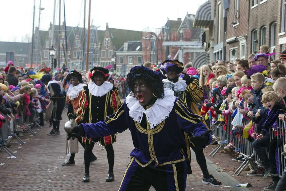 "FILE - In this Nov. 16, 2013 file photo a ""Zwarte Piet"" or ""Black Pete"", jokes with children after arriving with Sinterklaas, or Saint Nicholas, by steamboat in Hoorn, north-western Netherlands. Amsterdam's mayor and organizers of a large children's winter festival have unveiled plans on Thursday, Aug. 14, 2014 to reform the image of ?Black Pete? in order to remove perceived racist elements over a period of years. A large majority of the Netherlands' mostly-white population say Pete is a positive figure and deny any racial insult. But a court and racism experts have found his appearance offensive. (AP Photo/Peter Dejong, File) Photo: Peter Dejong, Associated Press"