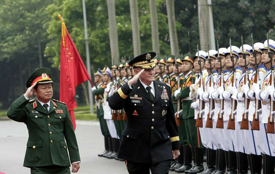 U.S. Chairman of the Joint Chiefs of Staff, Gen. Martin Dempsey, right, and Vietnamese Chief of General Staff of the Army, Lt. Gen. Do Ba Ty, left, review an honor guard before their talks in Hanoi, Vietnam on Thursday Aug. 14, 2014. Dempsey will hold talks with Vietnamese defense officials Wednesday on a visit that aims to boost military ties between the two former foes. (AP Photo/Tran Van Minh) Photo: Tran Van Minh, Associated Press