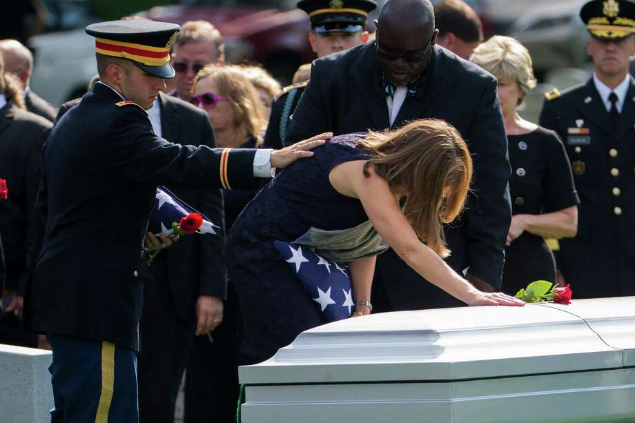 Army Lt. Matthew Greene, left, reaches out for his mother, retired Col. Susan Myers, as she places a rose on the casket of her husband, Army Maj. Gen. Harold Greene during a burial service at Arlington National Cemetery in Arlington, Va., Thursday, Aug. 14, 2014. Greene was killed when a gunman dressed as an Afghan soldier turned on ISAF troops, wounding about 15 including a German general and two Afghan generals. He is the highest-ranking U.S. military officer to be killed in either of America's post-9/11 wars. (AP Photo/Evan Vucci) Photo: Evan Vucci / AP