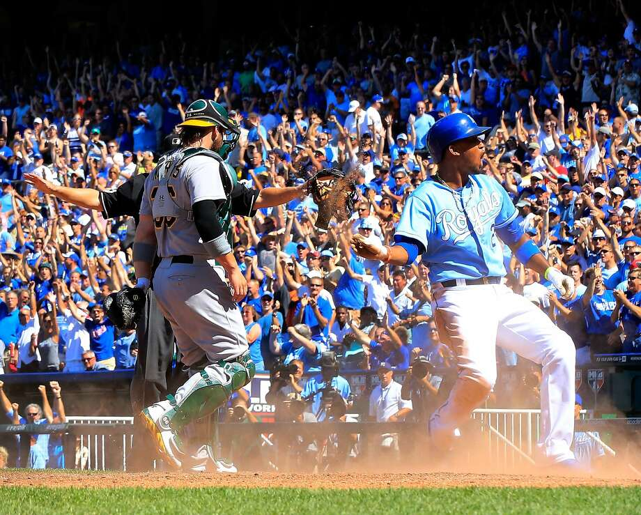 Kansas City's Alcides Escobar celebrates after sliding into home plate with the final run of the Royals' five-run seventh inning against the A's. Photo: Jamie Squire, Getty Images