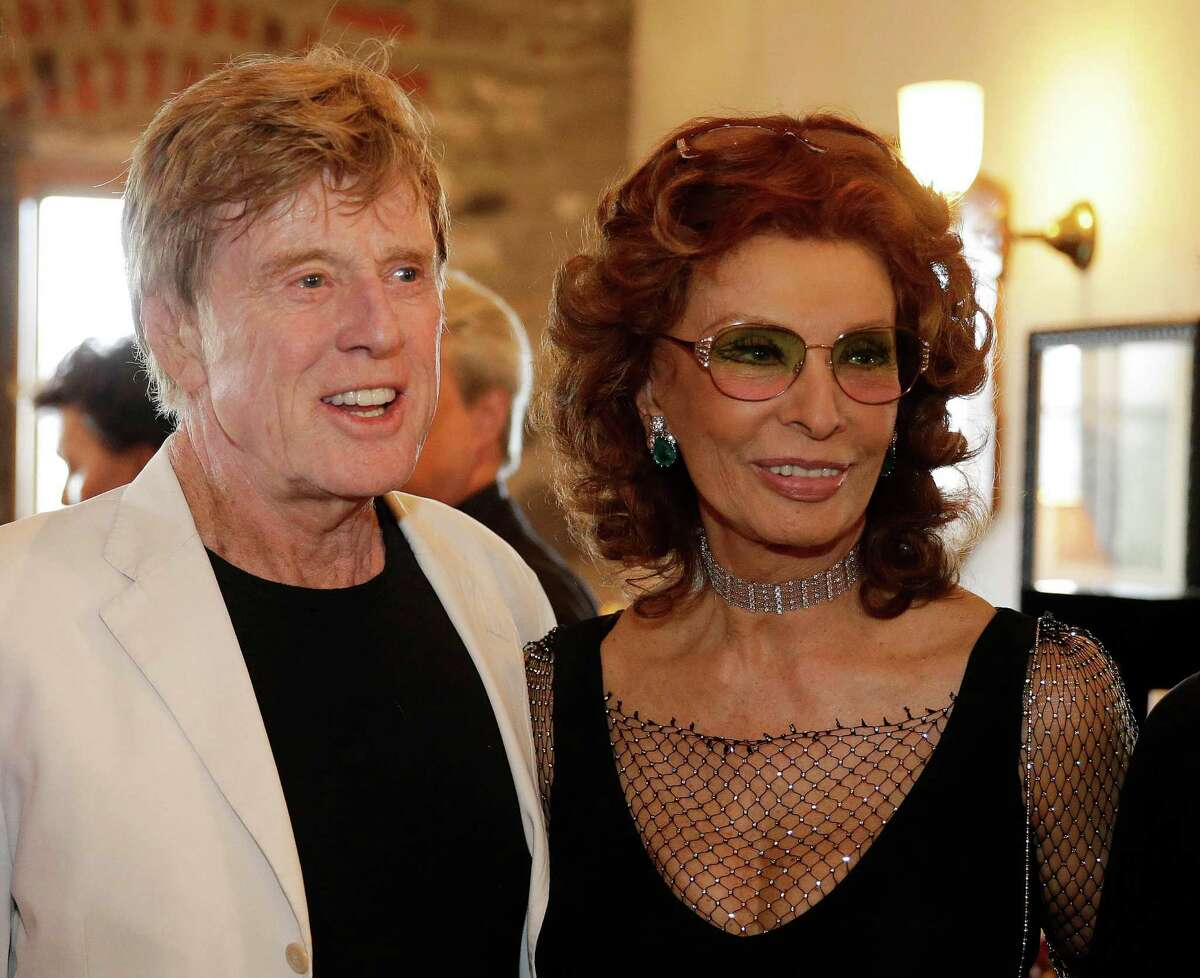"""Robert Redford, left, and Sophia Loren pose for pictures before the start of """"Bella Italia! a tribute to Sophia Loren"""" at the Far Niente winery Saturday, July 19, 2014, in Oakville, Calif. Loren turns 80 in September. The event is part of the Napa Valley Festival del Sole, a 10-day summer festival of music, theater and dance with the region's wine and cuisine. (AP Photo/Eric Risberg)"""