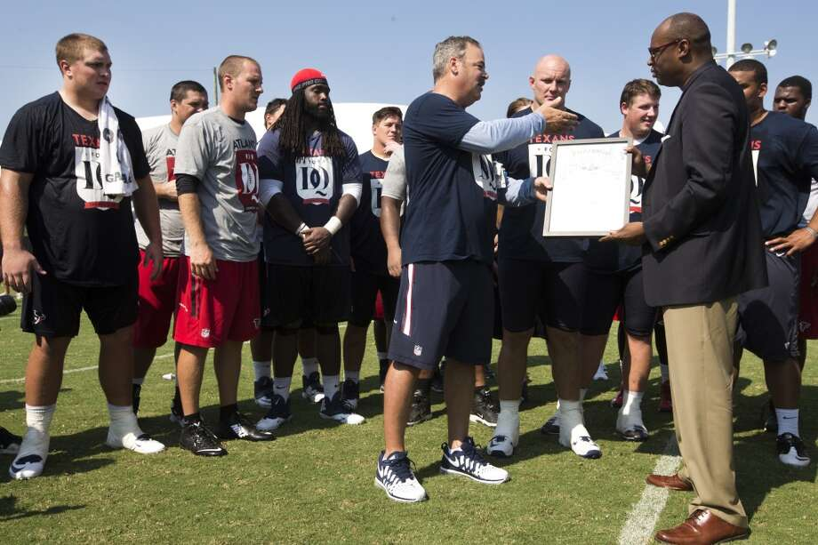 """Texans COO Cal McNair accepts a """"Texans for DQ Day"""" proclamation from Houston City Councilman Larry Greene following practice. """"Texans for DQ Day"""" honors Texans offensive tackle David Quessenberry who is battling lymphoma. Photo: Brett Coomer, Houston Chronicle"""