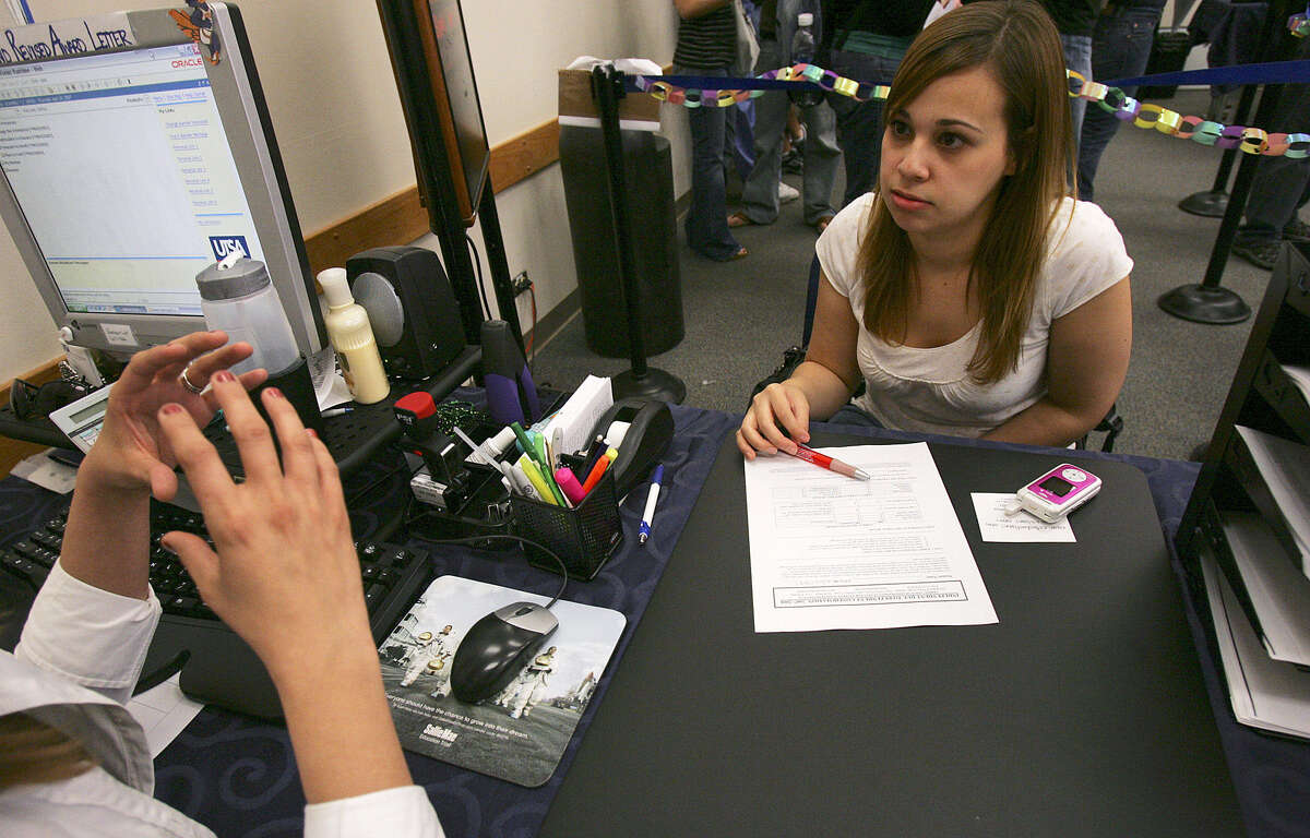 A student at the University of Texas at San Antonio talks to an enrollment service officer at the financial aid counter. In 2012, 1.3 million students graduated with college debt.