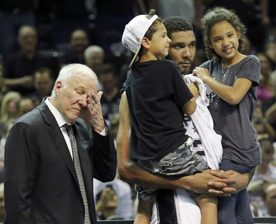 San Antonio Spurs' Tim Duncan holds his children, Draven (left) and Sydney, as head coach Gregg Popovich wipes away tears after clinching the 2014 NBA title against Miami. Photo: Edward A. Ornelas, San Antonio Express-News / © 2014 San Antonio Express-News