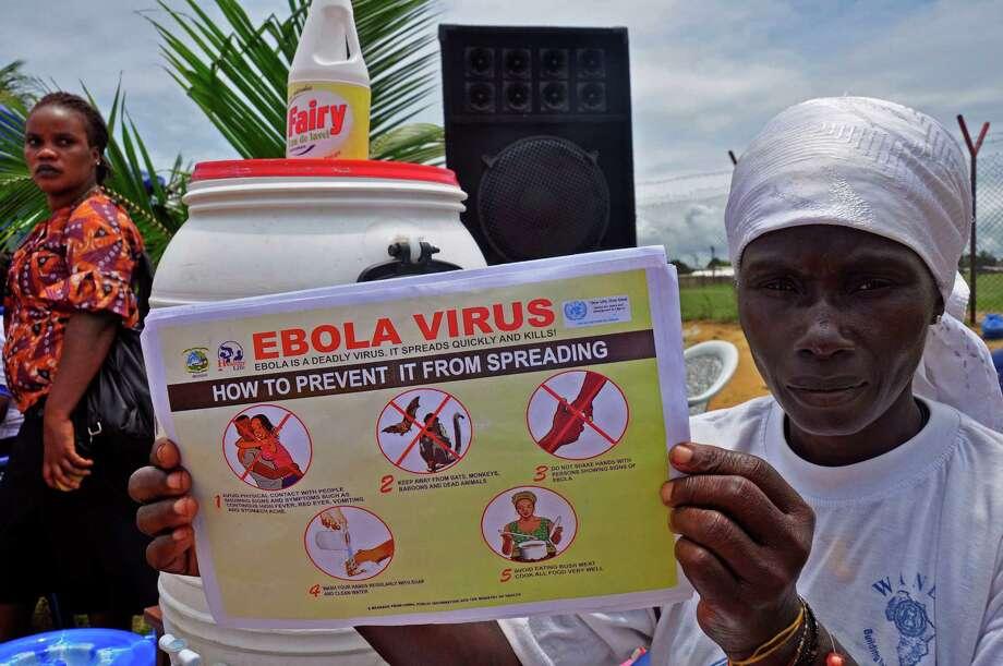 A Liberian woman holds up an Ebola pamphlet. Photo: Abbas Dulleh, STR / AP