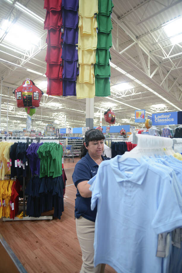 Wal-Mart employee Marisela Estrada arranges shirts, Thursday, Aug. 7,2014 in Brownsville for the annual tax free weekend.  (AP Photo/The Brownsville Herald, Brad Doherty) Photo: Brad Doherty, MBR / BROWNSVILLE HERALD