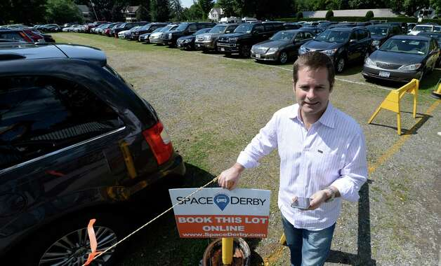 Hans Theisen holds his smart phone Thrusday afternoon, Aug. 14, 2014, which carries the app SpaceDerby.com that he developed for getting parking space at lots in Saratoga Springs, N.Y.    (Skip Dickstein/Times Union) Photo: SKIP DICKSTEIN / 00028172A