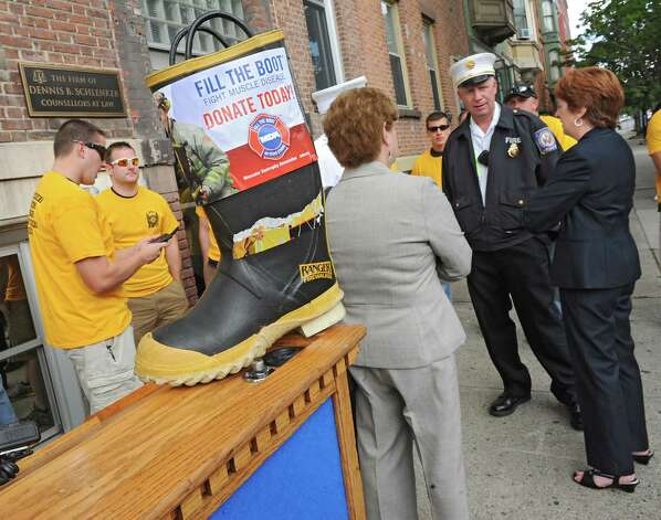 Albany Mayor Kathy Sheehan, right, is seen talking to firefighters and fire chiefs at a kick off for the firefighters' annual Fill the Boot fundraising campaign to benefit Muscular Dystrophy Association at the New York State Professional Fire Fighters Association Building on Thursday, Aug. 14, 2014 in Albany, N.Y. (Lori Van Buren / Times Union) Photo: Lori Van Buren / 00028108A