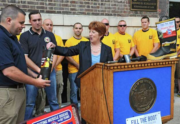 Albany Mayor Kathy Sheehan starts off the firefighters' annual Fill the Boot fundraising campaign to benefit Muscular Dystrophy Association by putting an inaugural bill into a boot held by Justin Gershon, MDA representative Albany Permanent Professional Firefighters Association Local 2007, on Thursday, Aug. 14, 2014 in Albany, N.Y. The press conference was held outside the New York State Professional Fire Fighters Association Building on Washington Ave. (Lori Van Buren / Times Union) Photo: Lori Van Buren / 00028108A