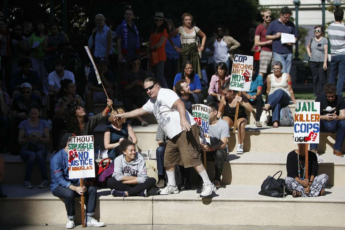 Frank Runninghorse distributes picket signs at a rally in support of Michael Brown on August 14, 2014 in Oakland, Calif.
