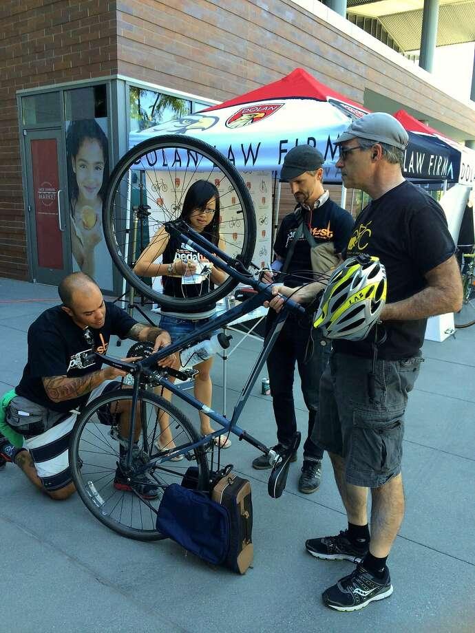 Charlie Fernandez-Hibbard (left), Janice Li and Robert Prinz register Ross Simkover's bicycle. Photo: Jenny Oh Hatfield