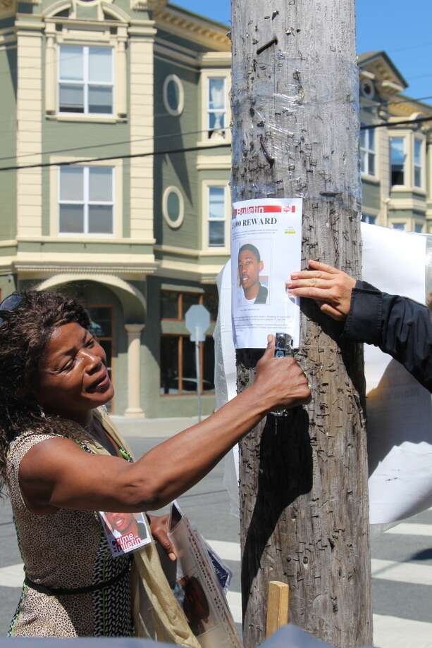 Paulette Brown staples a reward poster to a telephone pole near Baker and Grove streets in San Francisco. Despite a $250,000 reward for information leading to the arrest of her son's killer, no one has come forward and no arrests have been made. Photo: Kale Williams
