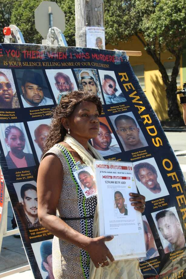 Paulette Brown holds a picture of her son, Aubrey Abrakasa, in front of a poster showing victims of gun violence. Photo: Kale Williams