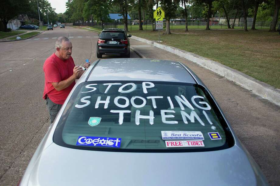 Dennis Woodward used his car at Shepherd Parkon Thursday to speak out  on the shooting of unarmed black Missouri teen Michael Brown. Photo: Johnny Hanson, Houston Chronicle / © 2014  Houston Chronicle