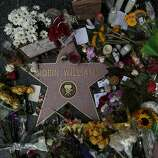 Flowers and memorabilia are piled on Robin Williams Hollywood Walk of Fame star in Los Angeles on Aug. 12, 2014, a day after he was found dead from an apparent suicide. (Robert Gauthier/Los Angeles Times/MCT)