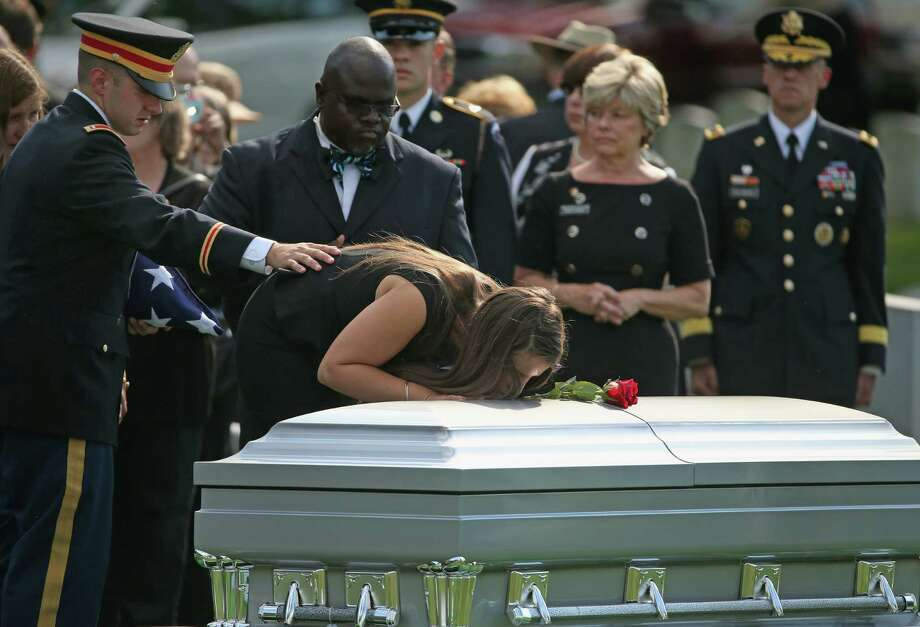 ARLINGTON, VA - AUGUST 14: 1st. Lt. Matthew Green (L) and his sister Amelia Green mourn at the casket of their father, U.S. Army Maj. Gen. Harold J. Greene during a full honors funeral service at Arlington National Cemetery, August 14, 2014 in Washington, DC. Greene was shot and killed as he visited Afghanistan's national military academy in Kabul, Afghanistan. He is the highest ranking Army officer killed in combat since the Vietnam War. (Photo by Mark Wilson/Getty Images) ORG XMIT: 507104097 Photo: Mark Wilson / 2014 Getty Images
