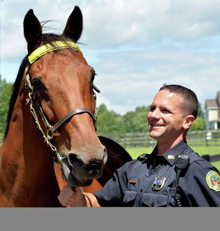 Saratoga Police officer Glenn Barrett stands with his partner 18 year old Jupiter Thursday afternoon Aug. 14, 2014 in Saratoga Springs, N.Y.    (Skip Dickstein/Times Union) Photo: SKIP DICKSTEIN / 00028166A