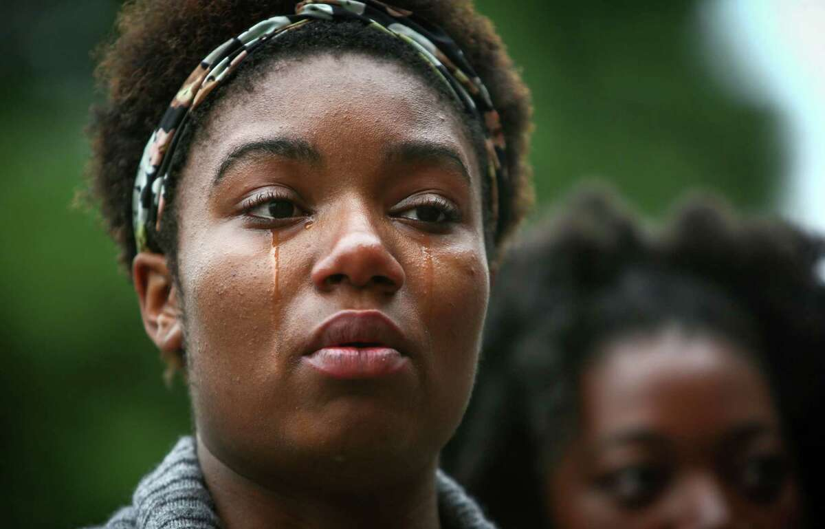 Zenobia Taylor, 17, becomes emotional during a National Moment of Silence against police brutality at Queen Anne Baptist Church on Thursday, August 14, 2014. Dozens gathered simultaneously at the church and at Westlake Park in Seattle. Across the country, people gathered to participate in the moments of silence after recent violence in Ferguson, Missouri and the shooting death of unarmed Mike Brown, a black man killed by a police officer there.
