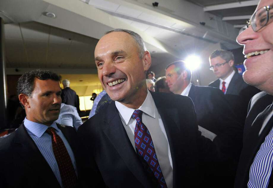 After several rounds of voting ultimately ended in his unanimous approval, Rob Manfred put on a happy face as the next commissioner of baseball. Photo: Steve Ruark, FRE / FR96543 AP