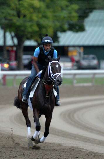 Stopchargingmaria, with exercise rider Nick Bush, works on the main track in preparation for Saturda