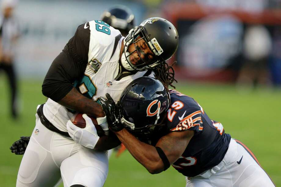 RETRANSMISSION TO CORRECT ID TO  DANNY MCCRAY - Jacksonville Jaguars tight end Marcedes Lewis (89) is tackled by Chicago Bears safety Danny McCray (29) after picking up a first down in the first half an NFL preseason football game in Chicago, Thursday, Aug. 14, 2014. (AP Photo/Michael Conroy) ORG XMIT: CXB103 Photo: Michael Conroy / AP