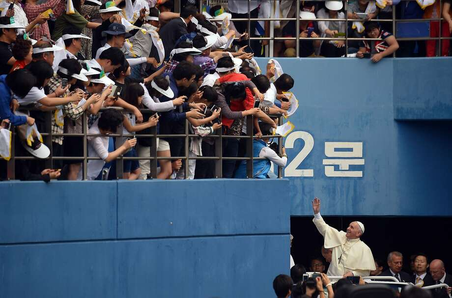 Pope Francis (right) gets a rock star-like welcome as he waves upon his arrival at the Daejeon World Cup Stadium to celebrate a public Mass with tens of thousands of followers. Photo: Vincenzo Pinto, AFP/Getty Images