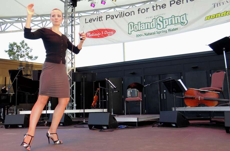 Tango instructor Olga Suarez Paz demonstrates dance steps to Levitt Pavilion visitors Thursday evening prior to the performance by her husband, Leonardo Suarez Pas, and his Cuartetango String Quartet. Photo: Mike Lauterborn / Westport News