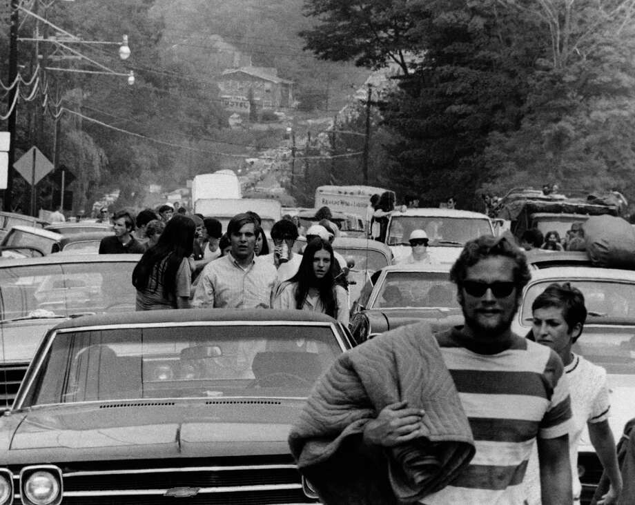 Young people abandon their trucks, cars and buses as some 200,000 persons try to reach the Woodstock Music and Art Festival on a leased cow pasture at White Lake in Bethel, New York Friday, Aug. 15, 1969. Cars were backed up for 10 miles. The festival closed the New York State Thruway, creating the nation?s worst traffic jam. (AP Photo) Photo: Anonymous, ASSOCIATED PRESS / AP1969