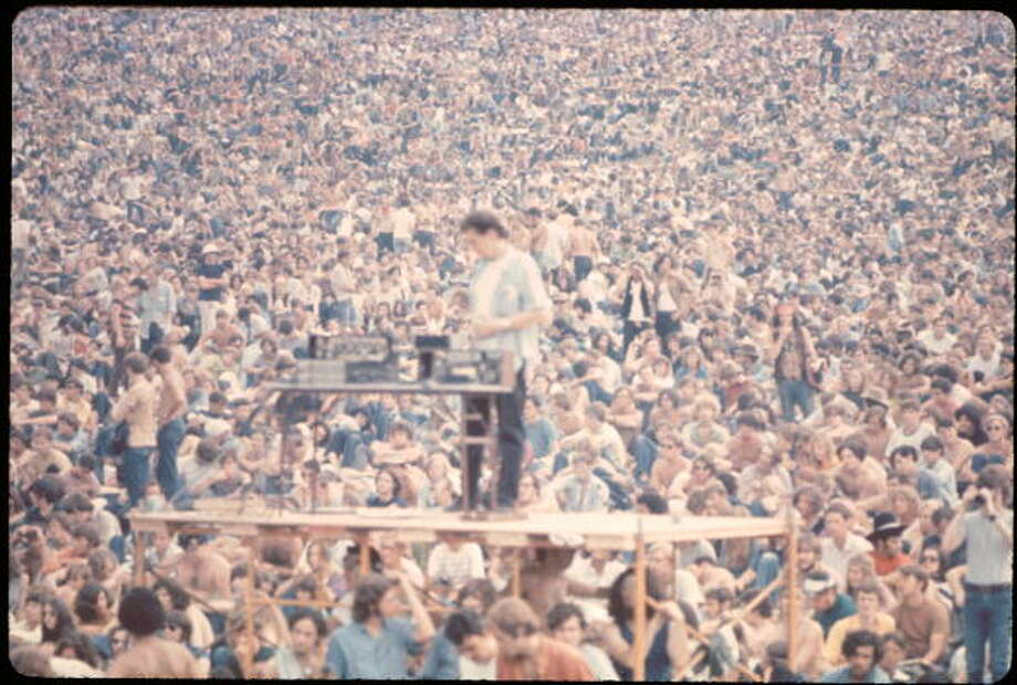 A sound guy stands on scaffolding with his equipment in front of the crowd at the Woodstock music festival, August 1969. Photo: Ralph Ackerman, (Getty Images) / Copyright 2009 Pat Ackerman